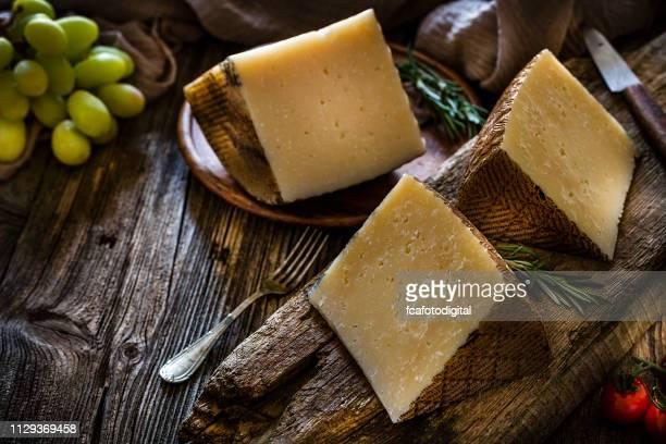 spanish food: manchego cheese pieces on rustic wooden table - queijo imagens e fotografias de stock