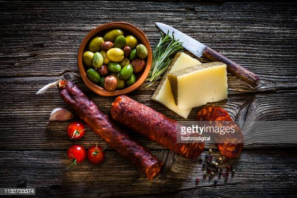 spanish food: manchego cheese, spanish chorizo and olives shot from above on rustic wooden table - antipasto stock pictures, royalty-free photos & images