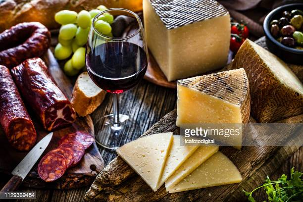 spanish food: manchego cheese, spanish chorizo and red wine on rustic wooden table - cheese stock pictures, royalty-free photos & images