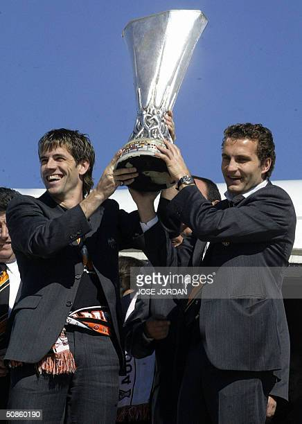 Spanish football club Valencia's players David Albelda and Ruben Baraja wave the UEFA Cup trophy upon their arrival at Valencia airport 20 May...