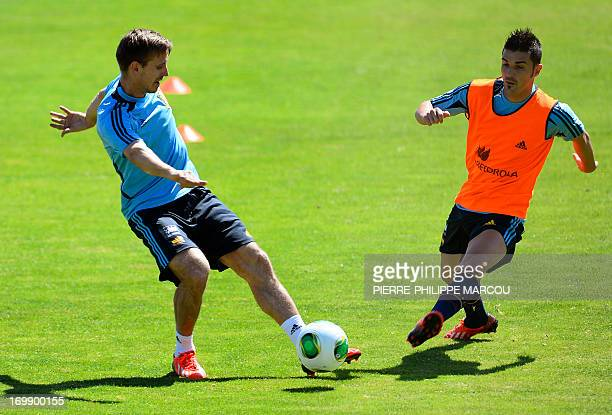 Spanish football player David Villa vies with Nacho Monreal during a training session in Las Rozas on June 4 2013 The world champions begin their...