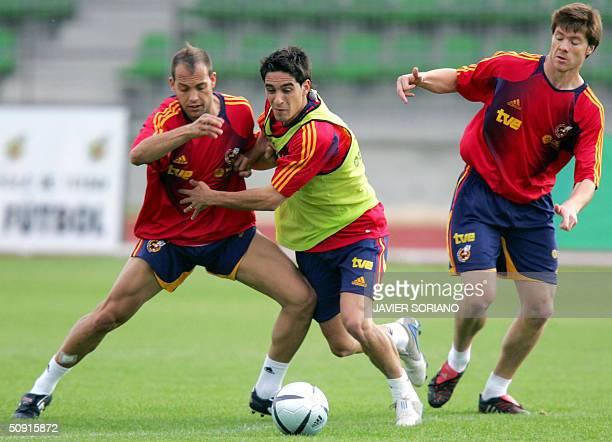 Spanish football players Gabriel Garcia 'Gabri' vies with Vicente Rodriguez and Xabi Alonso during an afternoon training session at Las Rozas...