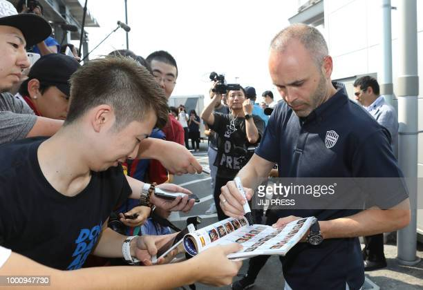 Spanish football star Andres Iniesta signs autographs as he is greeted by Vissel Kobe supporters upon his arrival at the Kansai International airport...