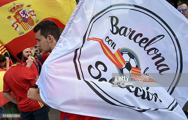 Spanish football team supporters hold a Spanish flag and a flag reading ' Barcelona with the selection' at Catalunya square in Barcelona on June 27...