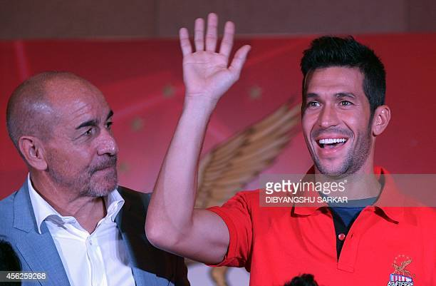 Spanish footballer Luis Garcia gestures as Atletico De Kolkata head coach Antonio Lopez Habas looks on during the launch of the football team for the...