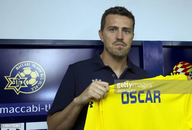 Spanish former footballer Oscar Garcia new manager coach of the Maccabi Tel Aviv football club holds up a team jersey with the name 'Oscar' in the...