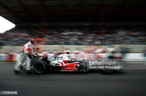 Spanish Formula One driver Fernando Alonso in his McLaren MP4-22 V8 Formula One car is pushed along the starting grid by his mechanics before the...