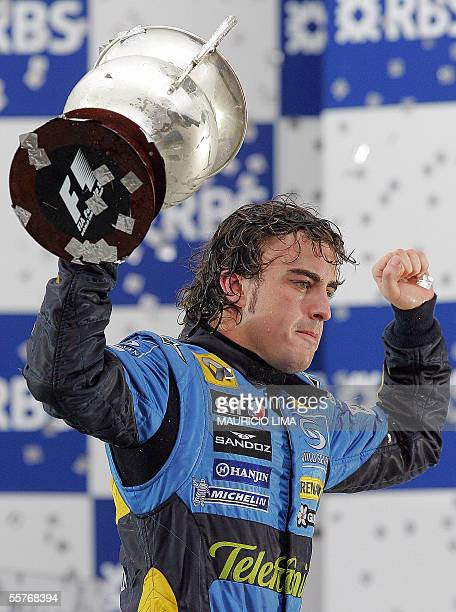 Spanish Formula One driver Fernando Alonso of Renault raises the trophy celebrating on the podium his F1 World Champion title obtained after arriving...
