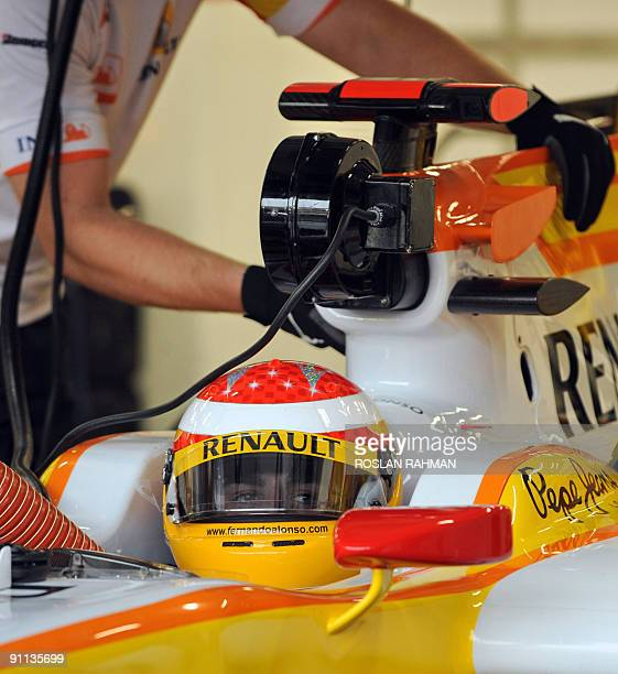 Spanish Formula One driver Fernando Alonso of Renault sits in his race car during the first practice session of the Singapore Formula One night race...