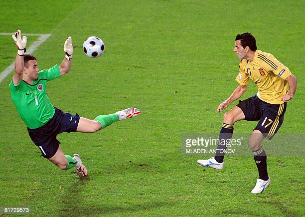 Spanish forward Daniel Guiza scores Spain's second goal in front of Russian goalkeeper Igor Akinfeev during the Euro 2008 championships semifinal...
