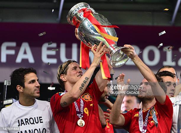 Spanish forward Fernando Torres holds the trophy and celebrates with team mates after winning the Euro 2012 football championships final match Spain...