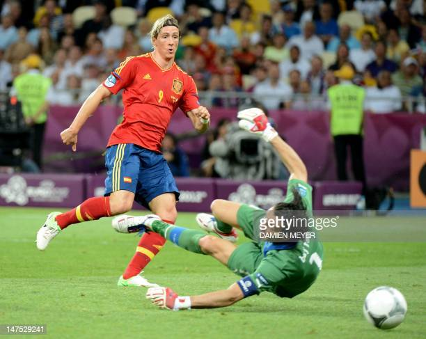 Spanish forward Fernando Torres scores against Italian goalkeeper Gianluigi Buffon during the Euro 2012 football championships final match Spain vs...