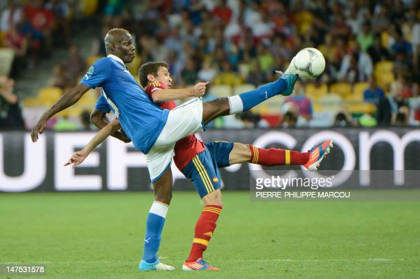 Spanish forward Juan Mata vies with Italian forward Mario Balotelli during the Euro 2012 football championships final match Spain vs Italy on July 1,...