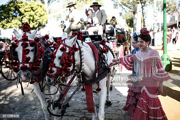Spanish girls in colorful flamenco dresses pose next to horses at the 'Feria de Abril 2016' the traditional Seville's Fair with 169 years of history...