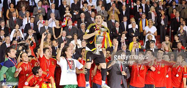 Spanish goalkeeper and captain Iker Casillas flanked by teammates celebrates with the trophy after the Euro 2008 championships final football match...