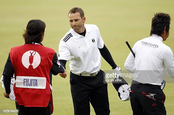 Spanish golfer Sergio Garcia shakes hands with Japanese golfer Hiroyuki Fujita's caddie on the 18th Green during his opening round on the first day...
