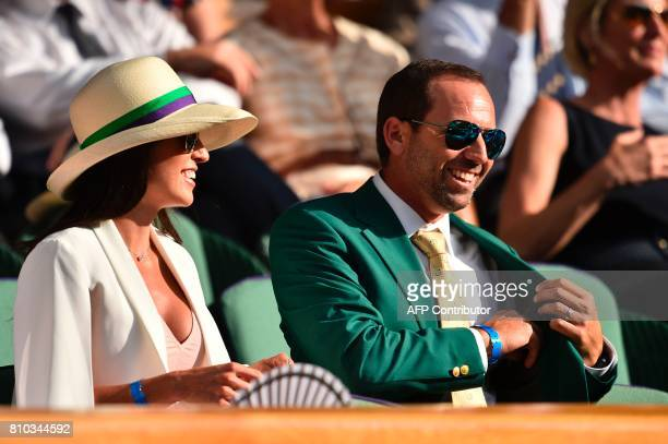 Spanish golfer Sergio Garcia wearing his Masters jacket is seen sitting with his partner Angela Akins in the Royal Box on Centre Court on the fifth...