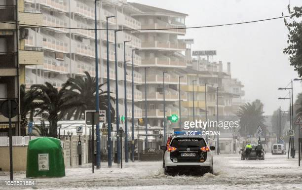 A Spanish Guardia civil car drives on a flooded street in Peniscola on October 19 during heavy rains that hit eastern Spain