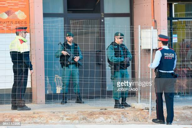 Spanish Guardia Civil guards and Catalan regional policemen Mossos d'Esquadra stand guard at the entrance of a building in Viladecans near Barcelona...