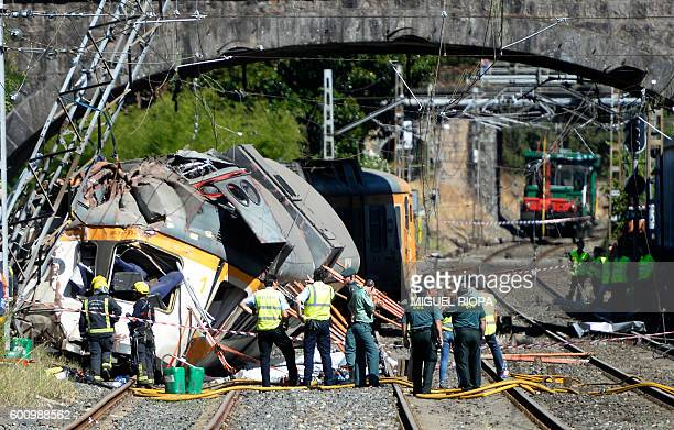TOPSHOT Spanish Guardia Civil policemen firefighters and security members stand past the wreckage of a train that derailed in O Porrino northwestern...