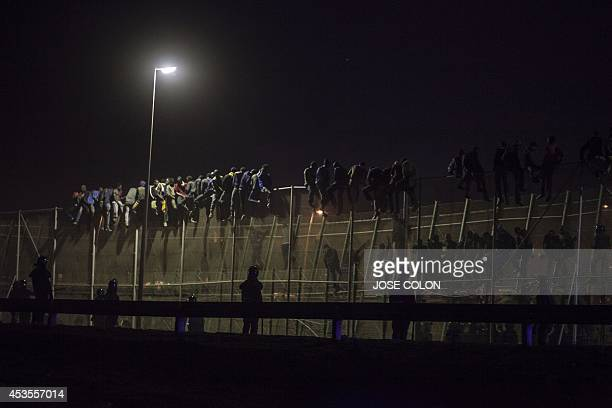 Spanish Guardia Civil watch as would be immigrants from Africa sit atop a wiremeche fence after scrambling over two other border barriers on Spain's...