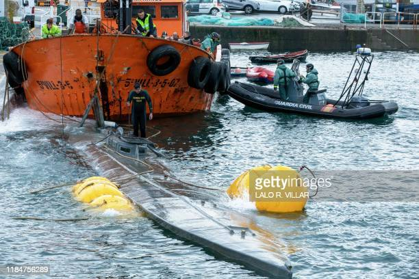 Spanish Guardia Civil's diver stands over the refloated prow of a submarine used to transport drugs illegally in Aldan, northwestern Spain, on...