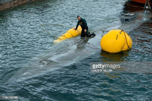 A Spanish Guardia Civil's diver stands over the refloated prow of a submarine used to transport drugs illegally in Aldan northwestern Spain on...