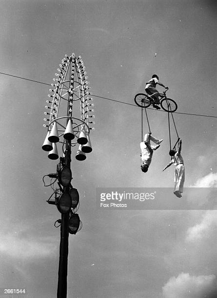 Spanish high wire cycling act The Mestelrich Trio performing high above Battersea Pleasure Gardens London