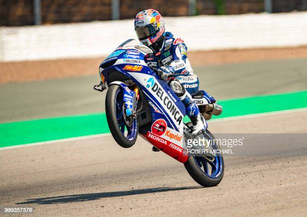 TOPSHOT Spanish Honda rider Jorge Martin pulls a wheelie after winning the Moto3 race at the Grand Prix of Germany at the Sachsenring Circuit on July...