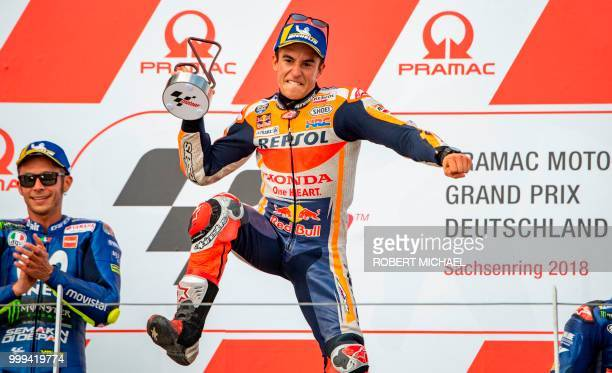 TOPSHOT Spanish Honda rider Marc Marquez celebrates in front of second placed Italian Yamaha rider Valentino Rossi on the podium after winning the...
