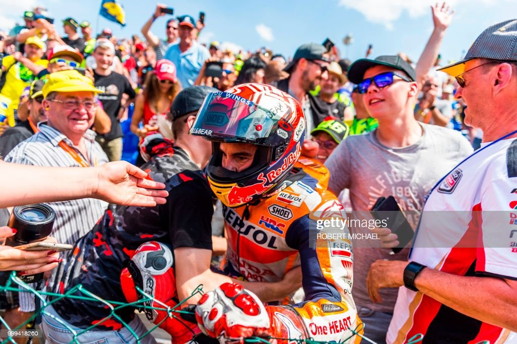 Spanish Honda rider Marc Marquez celebrates with supporters after winning the Moto GP race at the Grand Prix of Germany at the Sachsenring Circuit on July 15, 2018 in Hohenstein-Ernstthal, eastern Germany.
