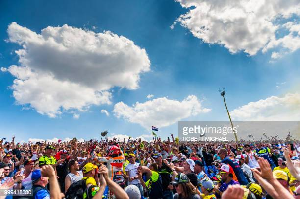 TOPSHOT Spanish Honda rider Marc Marquez celebrates with supporters after winning the Moto GP race at the Grand Prix of Germany at the Sachsenring...