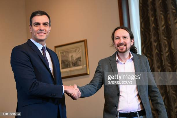 """Spanish incumbent prime minister Pedro Sanchez and leader of the left-wing electoral alliance """"Unidas Podemos"""" Pablo Iglesias shake hands during a..."""