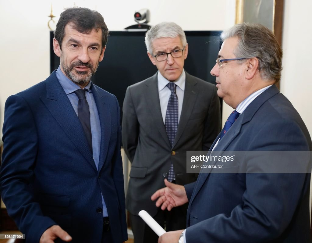 Spanish Interior Minister Juan Ignacio Zoido (R) talks with the new chief of 'Mossos D'Esquadra' (Catalan regional police) Ferran Lopez (L) beside Spanish Interior Ministry's Technical Secretary General, Juan Antonio Puigserver, in Madrid on October 30, 2017. Spain's Interior Minister, Juan Ignacio Zoido, met the new chief of the Mossos, Ferran Lopez, today, after the dischrge of former Catalan regional police chief Josep Lluis Trapero on October 28, 2017. / AFP PHOTO / POOL / ANGEL DIAZ / The erroneous mention[s] appearing in the metadata of this photo by ANGEL DIAZ has been modified in AFP systems in the following manner: [Ferran Lopez (L)] instead of [Ferran Lopez (C)]. Please immediately remove the erroneous mention[s] from all your online services and delete it (them) from your servers. If you have been authorized by AFP to distribute it (them) to third parties, please ensure that the same actions are carried out by them. Failure to promptly comply with these instructions will entail liability on your part for any continued or post notification usage. Therefore we thank you very much for all your attention and prompt action. We are sorry for the inconvenience this notification may cause and remain at your disposal for any further information you may require.