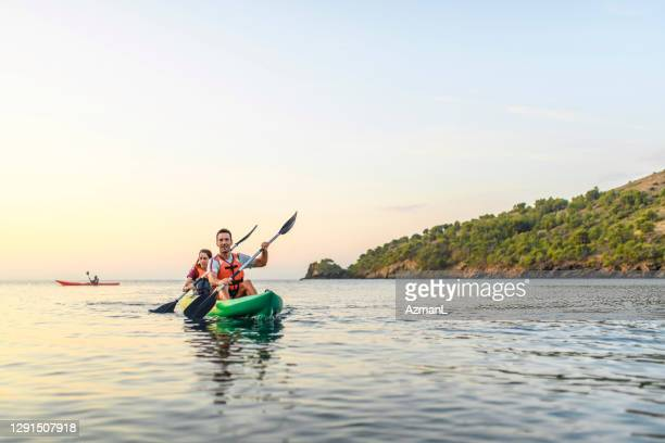spanish kayakers paddling in unison off the costa brava - sea kayaking stock pictures, royalty-free photos & images