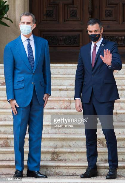 Spanish King Felipe VI greets Spanish Prime Minister Pedro Sanchez upon his arrival for a meeting at the royal family's summer residence at the...