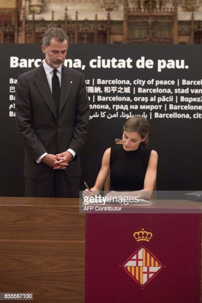Spanish king Felipe VI stands next to Spain's Queen Letizia signing the condolences book for the victims of the Barcelona and Cambrils attacks in the...