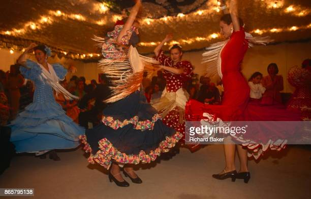 Spanish ladies dance Flamenco into the night at a private party in a marquee called a Caseta during the annual Feria de Abril on 11th June 1999 in...