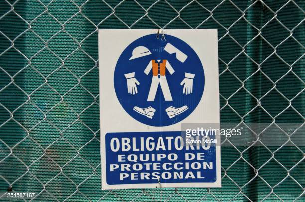 spanish language sign stating 'obligatorio equipo de protección personal' [mandatory personal protective equipment] on a wire fence around a construction site - protección stock pictures, royalty-free photos & images