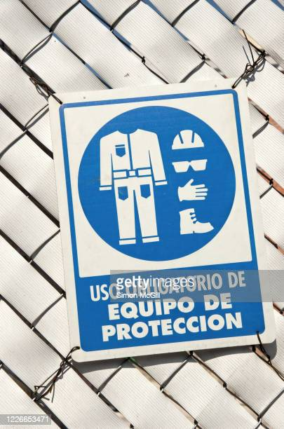 spanish language sign stating 'uso obligatorio de equipo de protección' [use of protective equipment is mandatory] on a wire fence with woven white plastic strips around a construction site - protección stock pictures, royalty-free photos & images