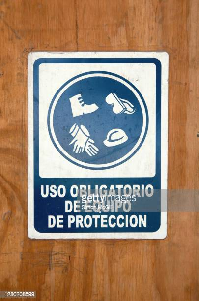 spanish language sign stating 'uso obligatorio de equipo de protección' [mandatory use of protective equipment] on a plywood fence around a construction site - protección stock pictures, royalty-free photos & images