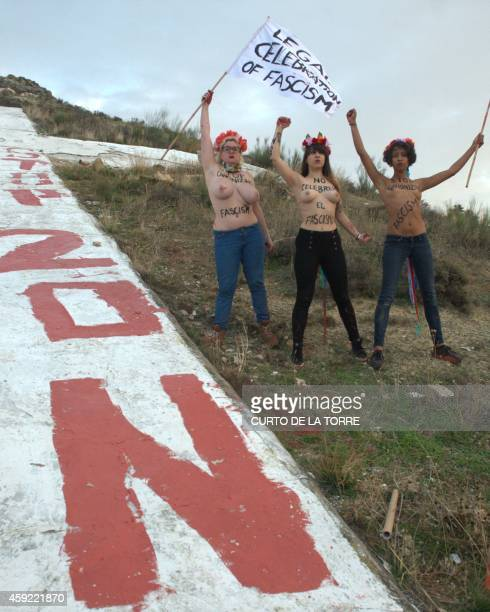Spanish leader of feminist movement Femen Lara Alcazar and two activists pose after painting a slogan reading 'Stop 20N' on a giant cross lying on...