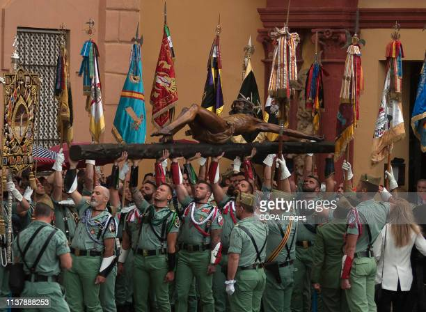 Spanish legionnaires are seen carrying a statue of 'Cristo de la Buena Muerte' also known as Christ of Mena under the rain during the Holy Week...
