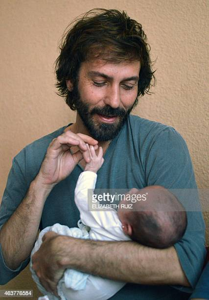 Spanish Luis Delgado poses with one fo his babies at home in the Cancun resort Mexico on February 18 2015 Luis and his partner Jose Antonio Fernandez...