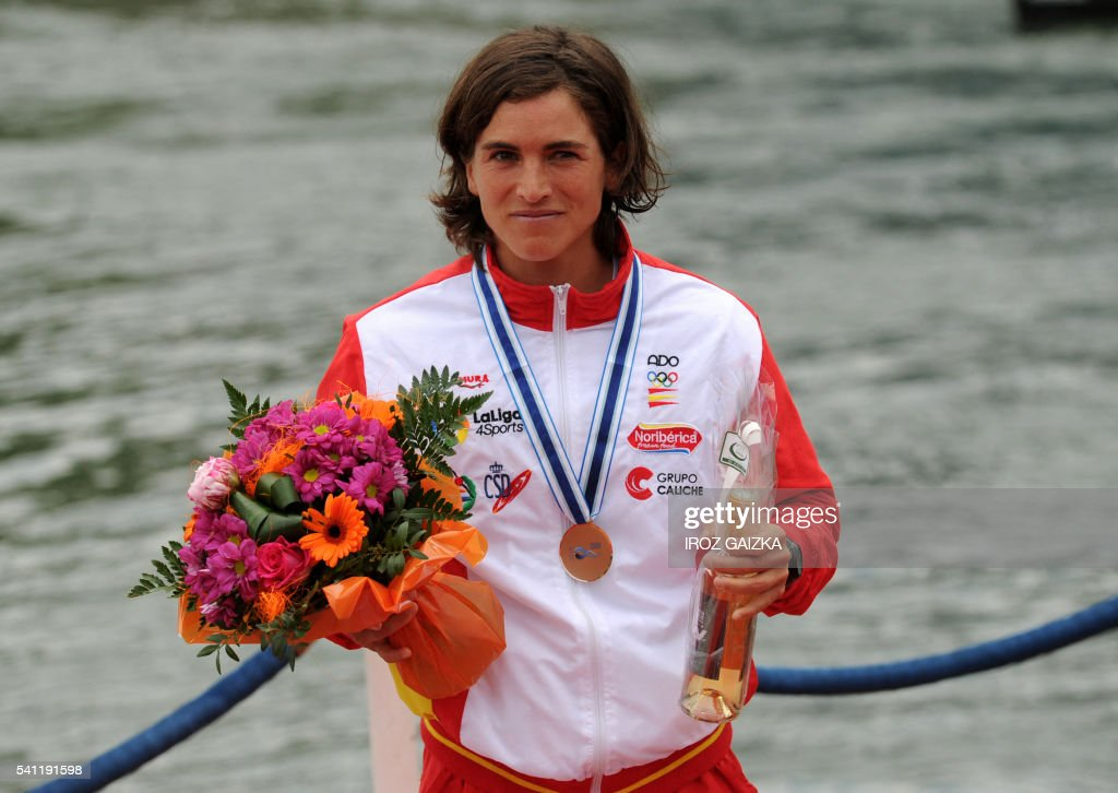 Spanish Maialen Chourraut celebrates on the podium of the women's slalom of the Worldcup Kayaking championships, in Pau, southwestern France on June 19, 2016. / AFP / IROZ