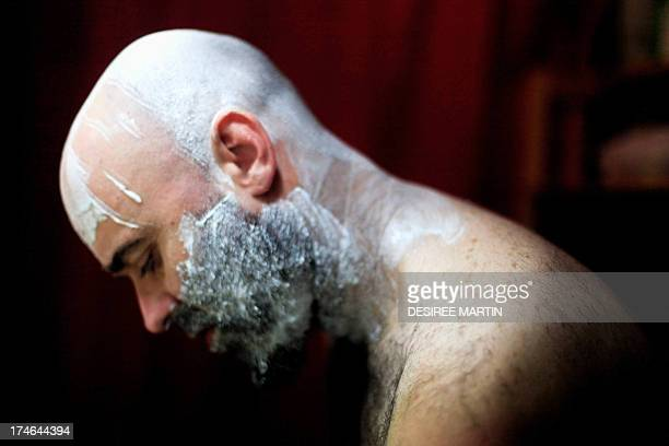 A Spanish man with shaving foam on his head and face is pictured in Santa Cruz on the Spanish Canary island of Tenerife on July 27 2013 AFP PHOTO/...