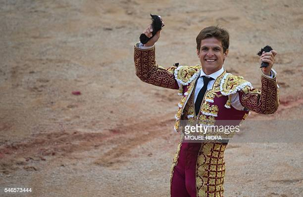 Spanish matador El Juli holds up two bull's ears during the sixth bullfight of the San Fermin Festival in Pamplona on July 12 2016 The festival is a...