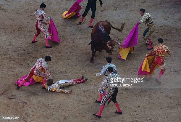 TOPSHOT Spanish matador Javier Fernandez lies on the ground after being hurled by a bull during the second bullfight of the San Fermin Festival at...