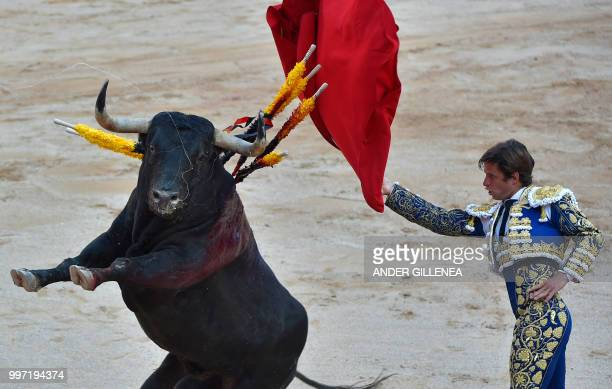 TOPSHOT Spanish matador Julian Lopez 'El Juli' performs a pass to a Victoriano del Rio fighting bull during a bullfight of the San Fermin festival in...