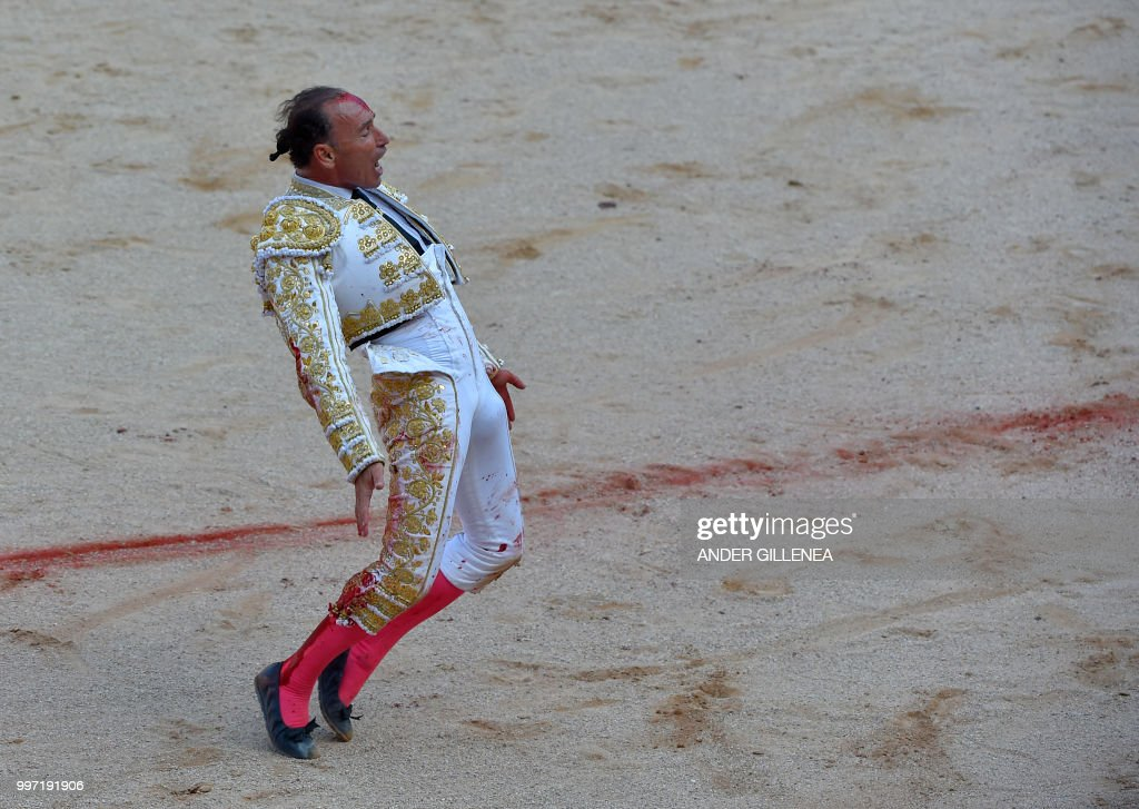 Spanish matador Pepin Liria gestures after being tossed by a Victoriano del Rio fighting bull during a bullfight of the San Fermin festival in Pamplona, northern Spain on July 12, 2018. - Each day at 8am hundreds of people race with six bulls, charging along a winding, 848.6-metre (more than half a mile) course through narrow streets to the city's bull ring, where the animals are killed in a bullfight or corrida, during this festival dating back to medieval times and also featuring religious processions, folk dancing, concerts and round-the-clock drinking.